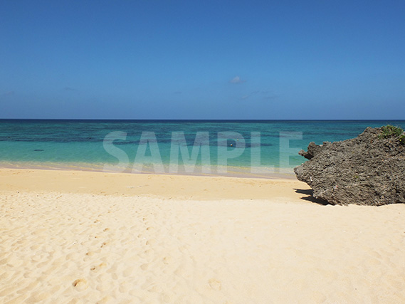 石垣島の青い海と砂浜と大きな岩