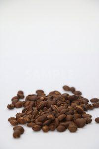 上部に白い余白のあるコーヒー豆が積まれた写真