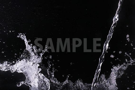 黒背景の水が注がれこぼれる写真・フォト