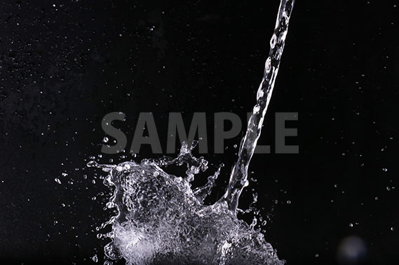 黒背景の水が注がれ飛び散る写真・フォト