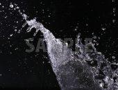 黒背景の水が勢い良く散布する写真・フォト