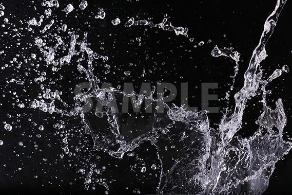 黒背景の水が四方に散布する写真・フォト
