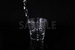 水が注がれるロックグラスの写真・フォト素材