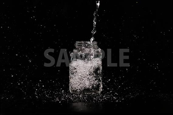 水が注がれる透明瓶の写真・フォト素材