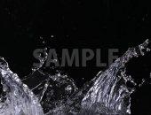 黒背景の水が左右に弾ける写真・フォト