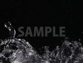 黒背景の水がほとばしる写真・フォト