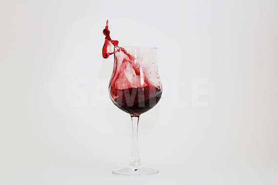 グラスから飛び出る赤ワインの写真・フォト