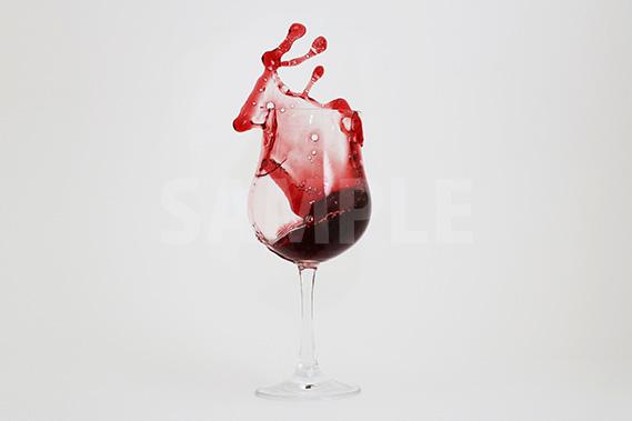 グラスから赤ワインが飛び散る写真・フォト