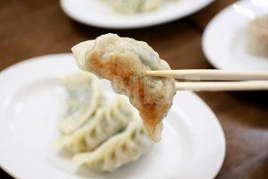 餃子を箸で持った写真・フォト素材